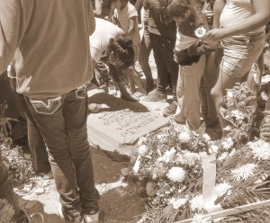 At the burial, writing on the fresh cement of the grave