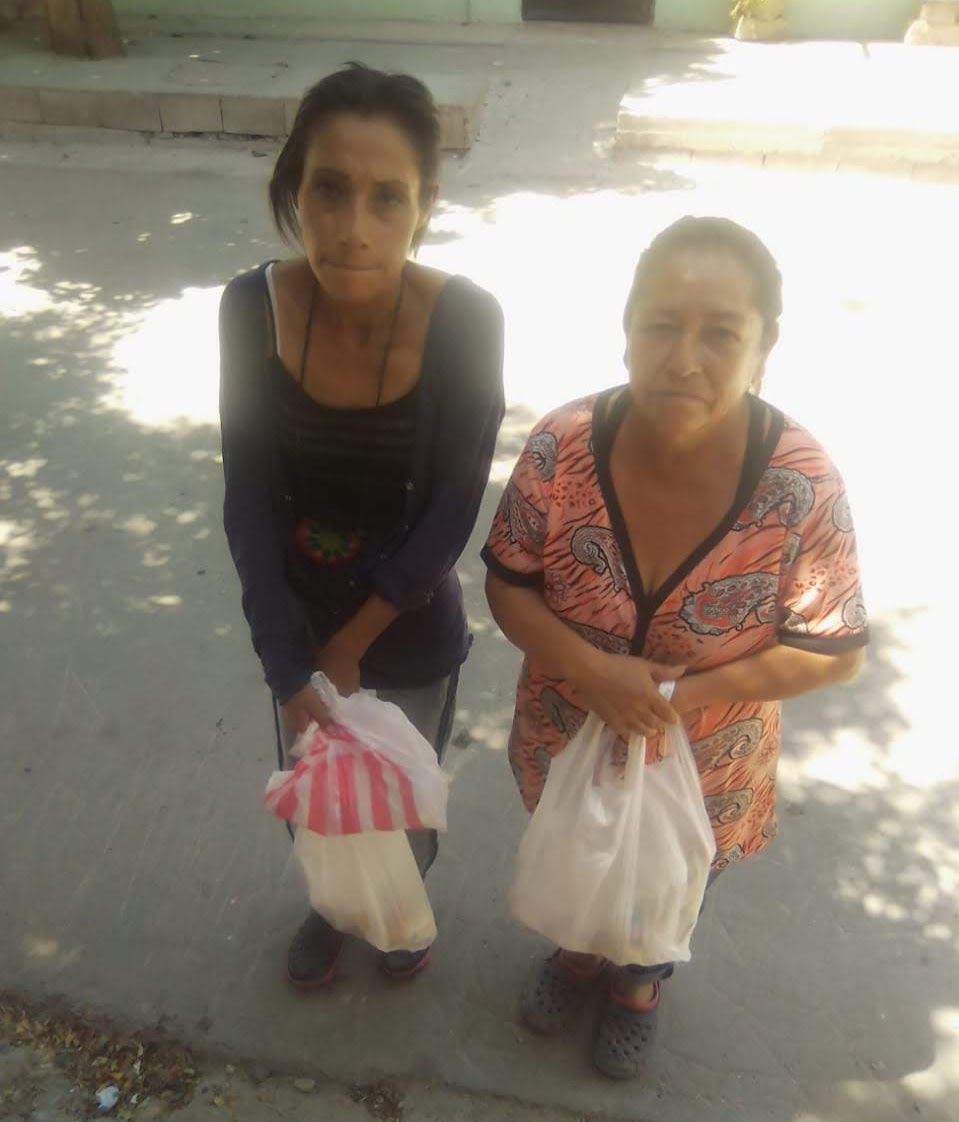 Two Mexican ladies, one older and one younger, each holding a bag of groceries